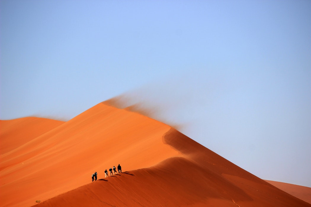 sand dune in desert being blown by sand with people walking along its ridge